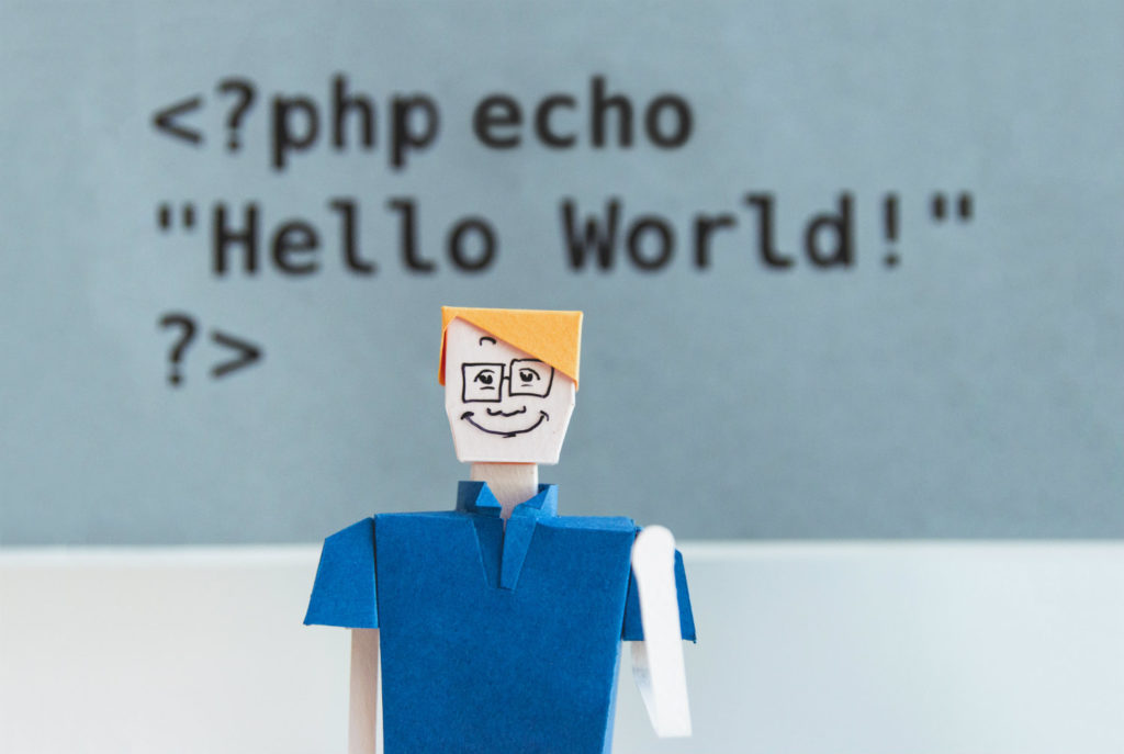 Paper figure of a man against the background of the php code