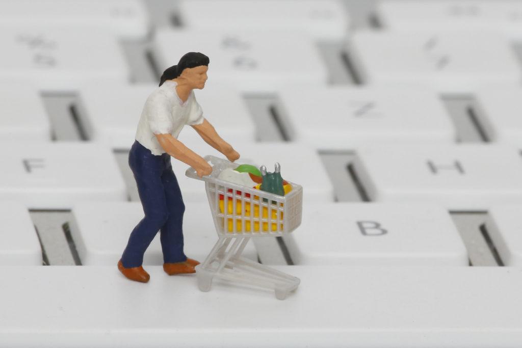 plastikowa figurka stojąca na klawiaturze. Figurka prezentuje człowieka z wózkiem pełnym zakupów