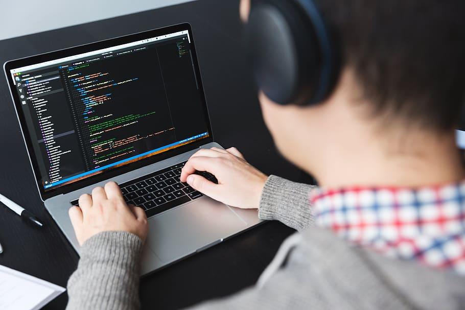mężczyzna w słuchawkach piszący kod na macbooku