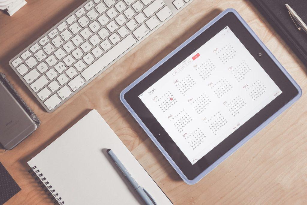 tablet, notes, długopis, klawiatura i telefon na biurku