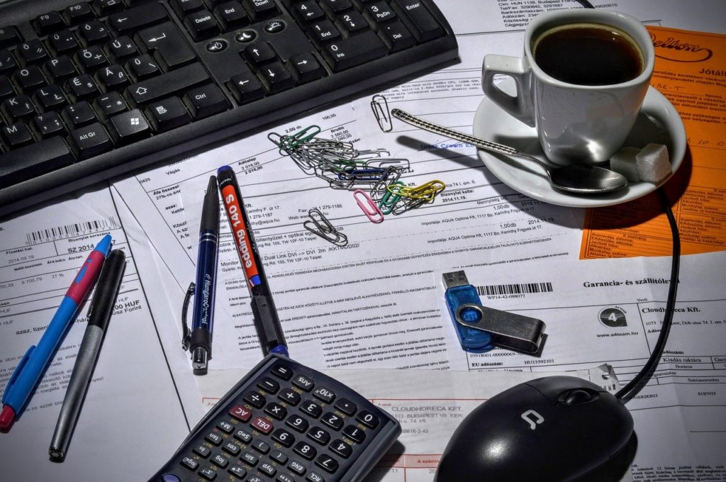 klawiatura, myszka komputerowa, pendrive, długopisy, dokumenty i filiżanka z kawą na biurku