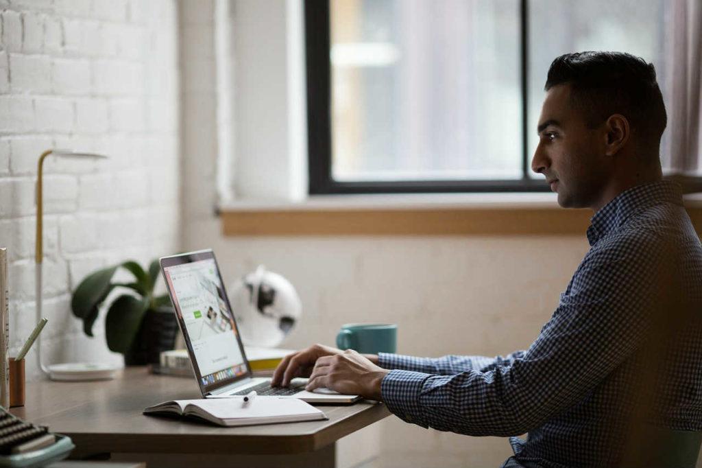 młody mężczyzna pracujący przy biurku na laptopie