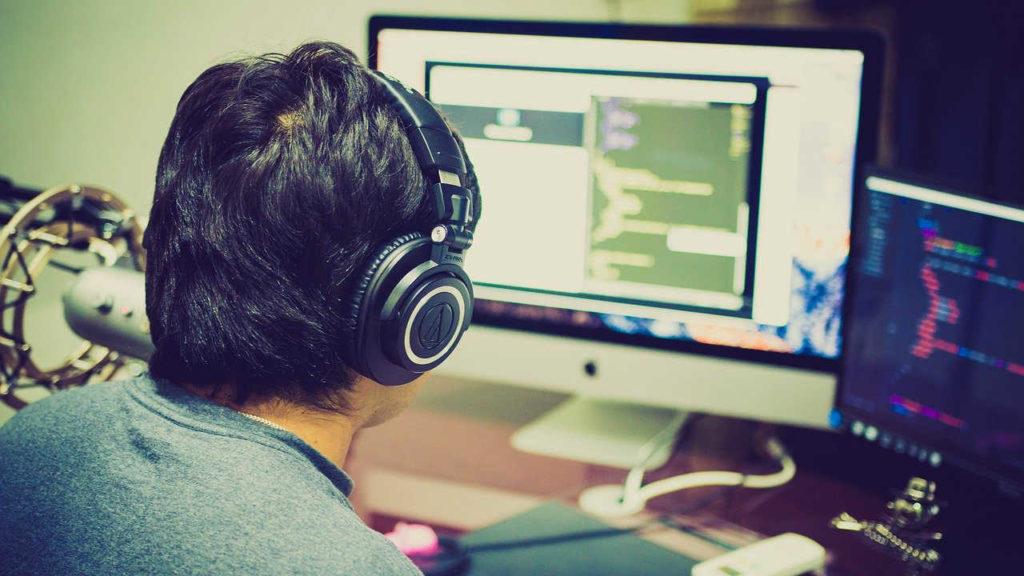 mężczyzna w słuchawkach pracujący przy komputerze