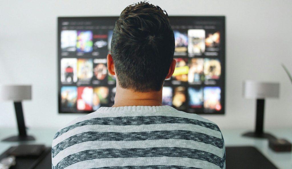 mężczyzna przeglądający filmy na ekranie telewizora